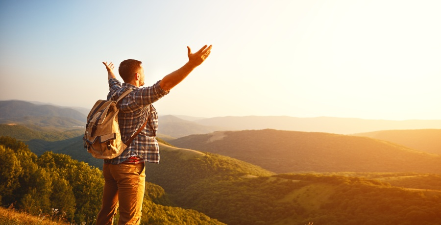 man with open arms facing the sunset over a valley of hills